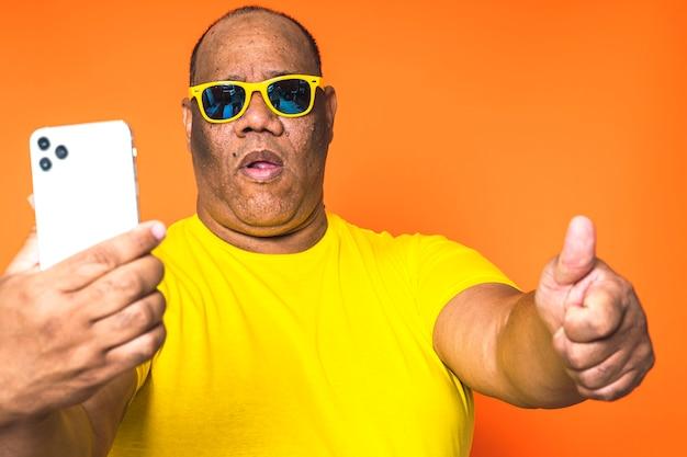 Uomo di colore che per mezzo del telefono cellulare su fondo isolato