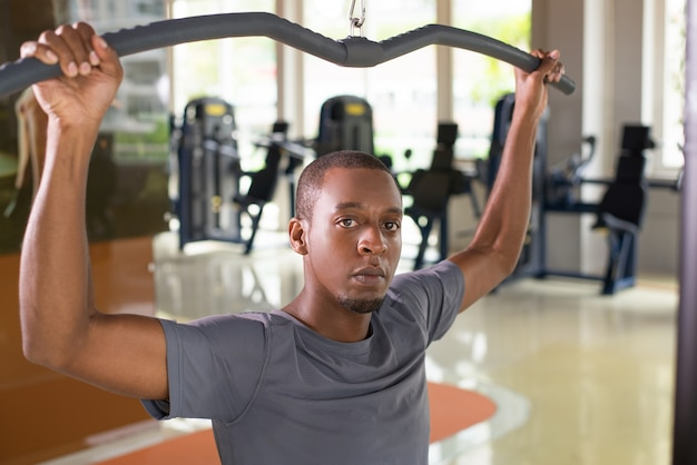 Uomo di colore che si esercita sulla macchina del pull down del lat