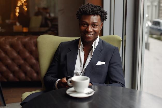 Uomo di colore che si siede in un caffè e che beve un caffè
