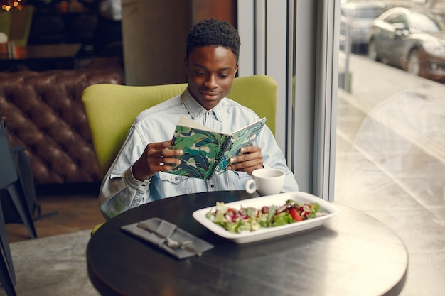Uomo di colore che si siede in un caffè e che mangia un'insalata di verdure