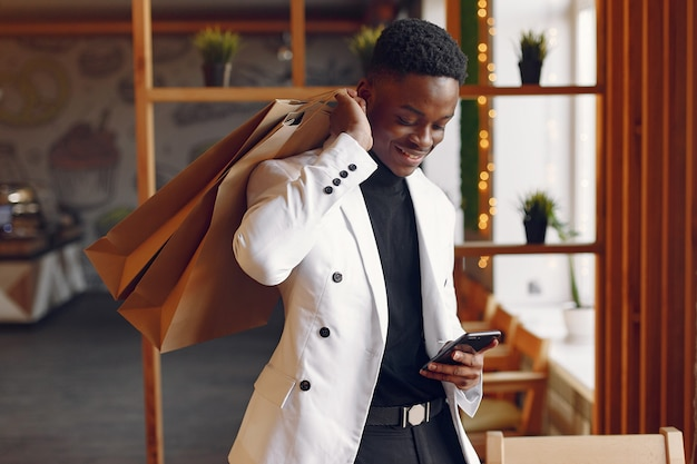 Uomo di colore che sta in un caffè con i sacchetti della spesa