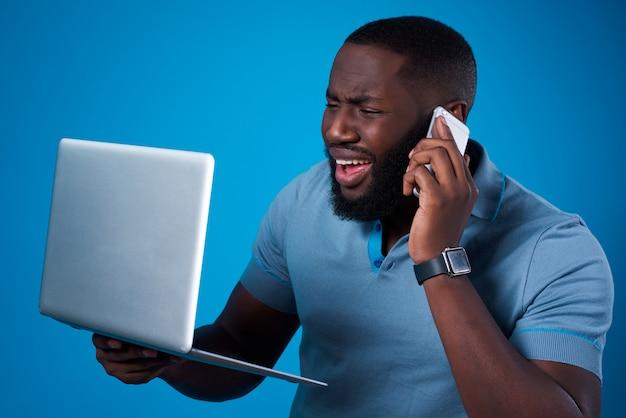 Uomo di colore con laptop e telefono.