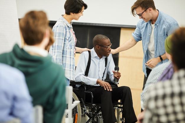 Uomo di colore disabile in sedia a rotelle che dà conferenza alla conferenza