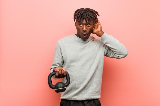 Uomo di colore giovane fitness in possesso di un manubrio cercando di ascoltare un gossip.