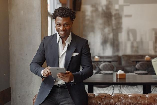 Uomo di colore in un abito nero in piedi in un caffè