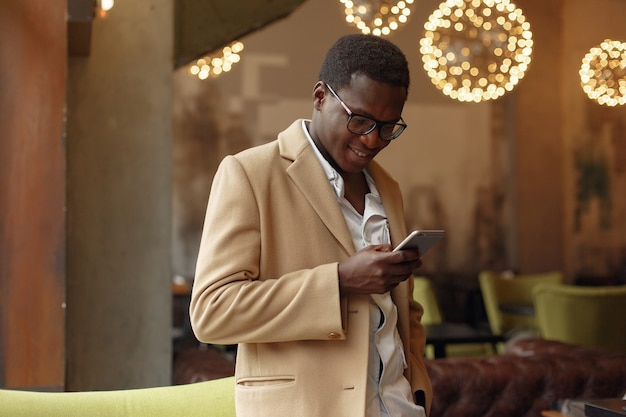 Uomo di colore in un cappotto marrone che sta con il telefono cellulare