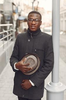 Uomo di colore in un cappotto nero in una città di autunno