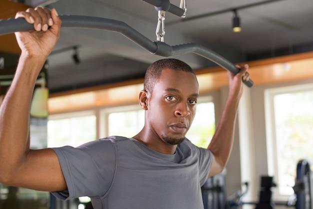 Uomo di colore serio che si esercita sulla macchina di abbattimento del lat