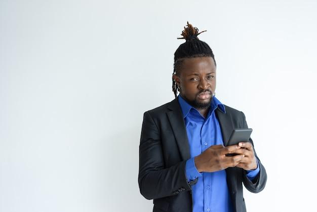 Uomo di colore serio che tiene e che usando smartphone