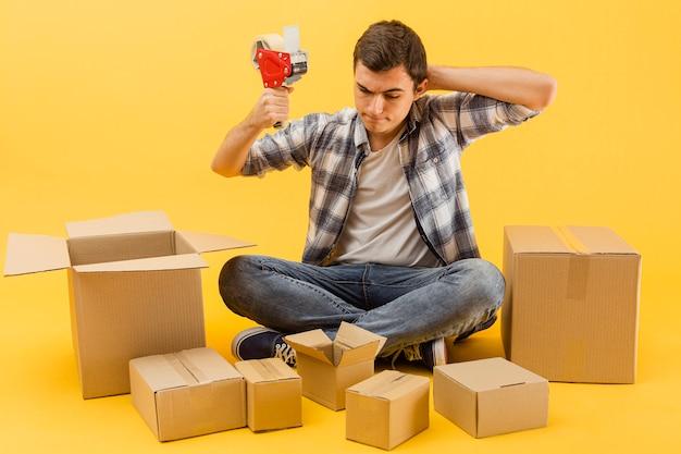 Uomo di consegna ad alto angolo preparato per avvolgere i pacchi di consegna