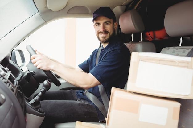 Uomo di consegna alla guida del suo furgone con pacchetti sul sedile anteriore