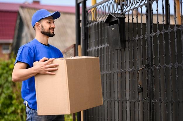 Uomo di consegna barbuto felice di distribuire il pacco