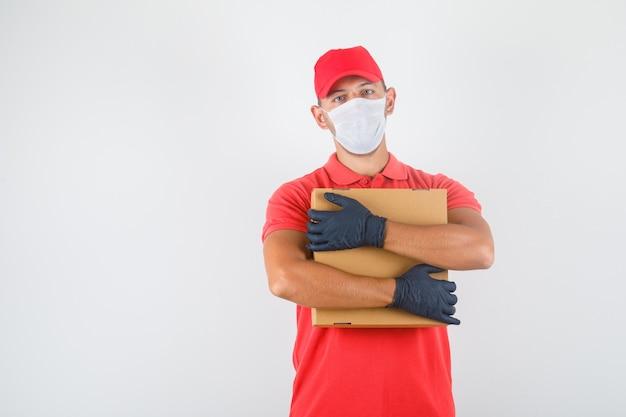 Uomo di consegna che abbraccia la scatola di cartone in uniforme rossa, mascherina medica, guanti e che sembra fiducioso