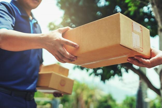 Uomo di consegna che consegna la scatola del pacco della tenuta al cliente