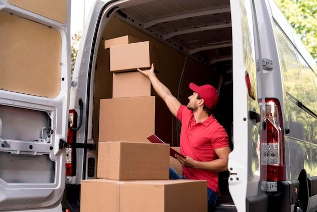 Uomo di consegna che controlla i pacchetti