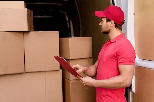 Uomo di consegna che controlla la lista dei pacchetti