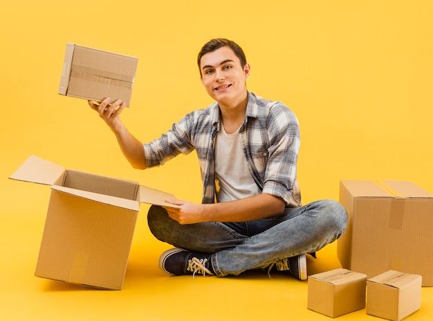 Uomo di consegna che controlla le scatole d'imballaggio