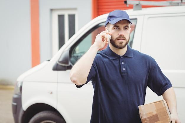 Uomo di consegna che fa una telefonata mentre si tiene un pacchetto