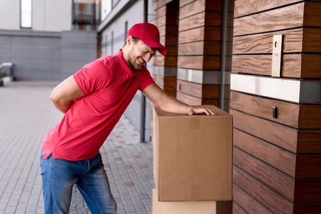 Uomo di consegna che ha mal di schiena da trasportare