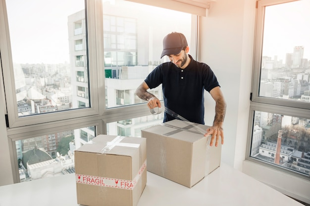 Uomo di consegna che imballa la scatola di cartone