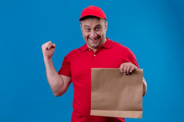 Uomo di consegna che indossa l'uniforme rossa e cappuccio che tiene il fronte sorridente del pacchetto di carta che alza il pugno dopo una vittoria che sta sopra lo spazio blu isolato
