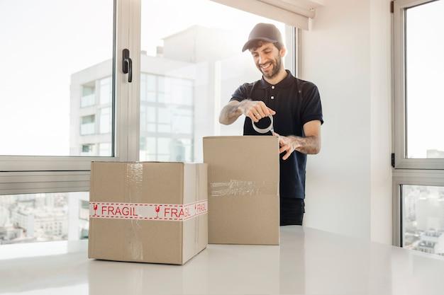 Uomo di consegna che lega su scatole di cartone