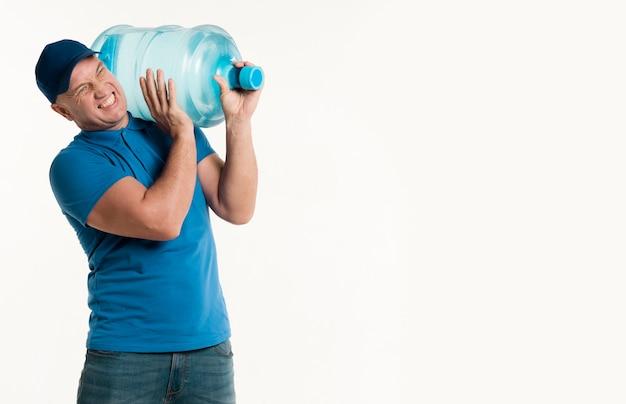 Uomo di consegna che porta una bottiglia di acqua pesante sulla spalla