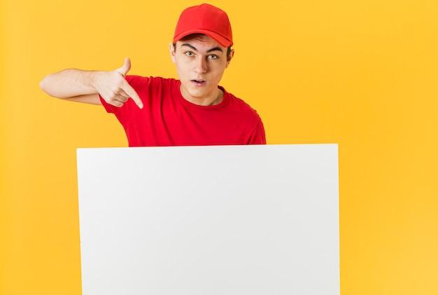 Uomo di consegna che punta al foglio di carta bianca