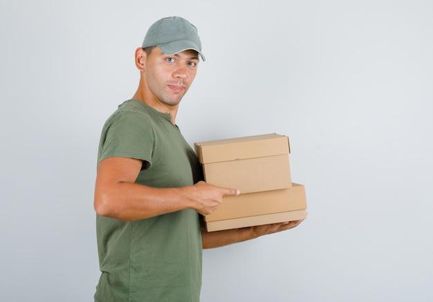 Uomo di consegna che punta il dito contro scatole di cartone in maglietta verde, cappuccio.