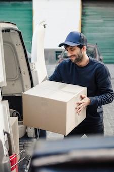 Uomo di consegna che scarica la scatola di cartone dal veicolo