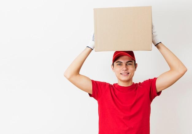 Uomo di consegna che tiene il pacchetto sopra la testa
