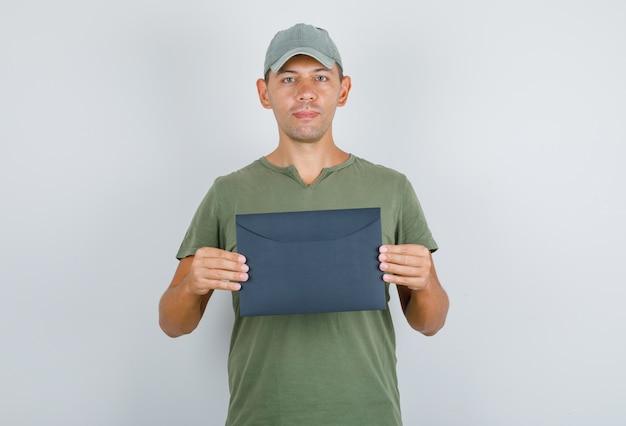 Uomo di consegna che tiene il pacco in maglietta verde militare, cappuccio, vista frontale.