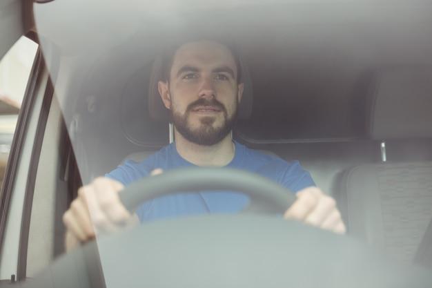 Uomo di consegna che tiene il volante per guidare il suo furgone