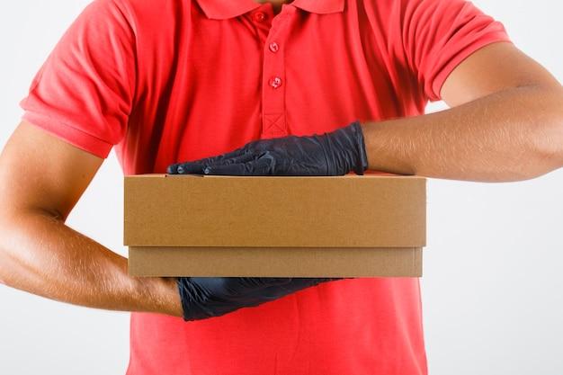 Uomo di consegna che tiene la scatola di cartone in uniforme rossa, guanti medicali, vista frontale.