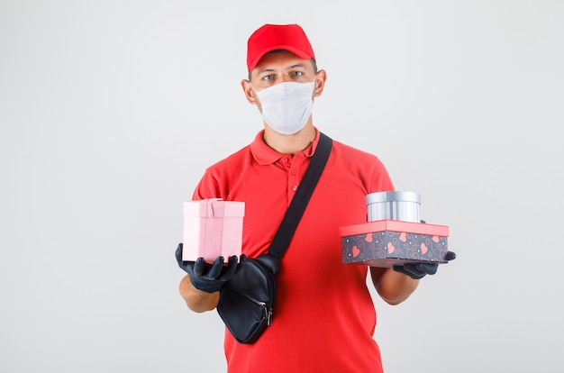 Uomo di consegna che tiene le caselle presenti in uniforme rossa, mascherina medica, vista frontale dei guanti.