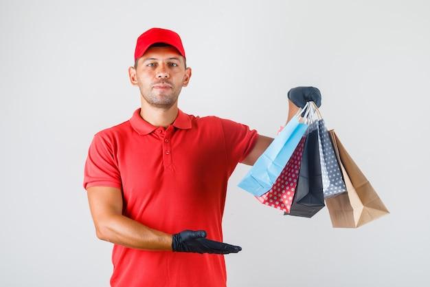 Uomo di consegna che tiene pila di sacchetti di carta in uniforme rossa, vista frontale guanti.