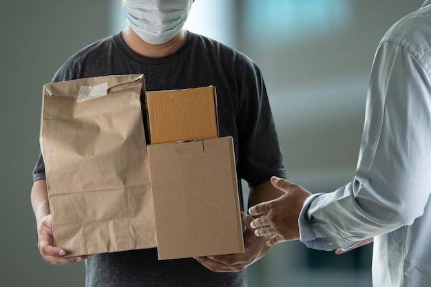 Uomo di consegna che tiene scatole di cartone e che accetta uomo di consegna in maschera protettiva
