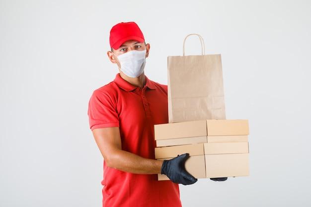 Uomo di consegna che tiene scatole di cartone e sacchetto di carta in uniforme rossa, mascherina medica, vista frontale dei guanti.