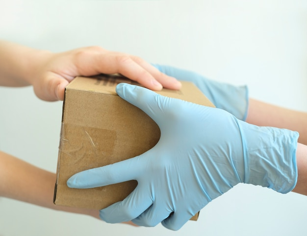 Uomo di consegna che tiene scatole di cartone in guanti di gomma medica.