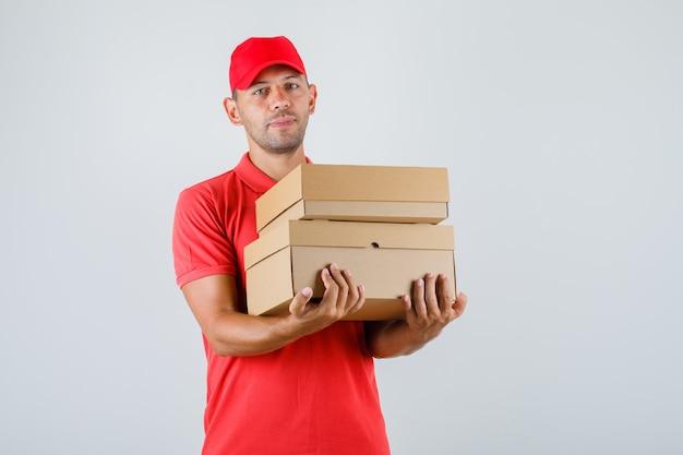 Uomo di consegna che tiene scatole di cartone in uniforme rossa, vista frontale.