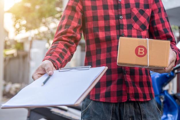 Uomo di consegna che tiene scatole di cartone.