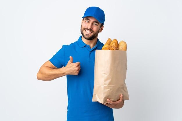 Uomo di consegna che tiene una borsa piena di pane isolato su bianco con i pollici in su perché è successo qualcosa di buono