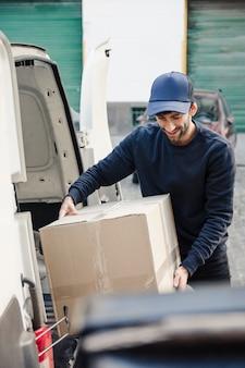 Uomo di consegna che trasporta la scatola di cartone dal veicolo