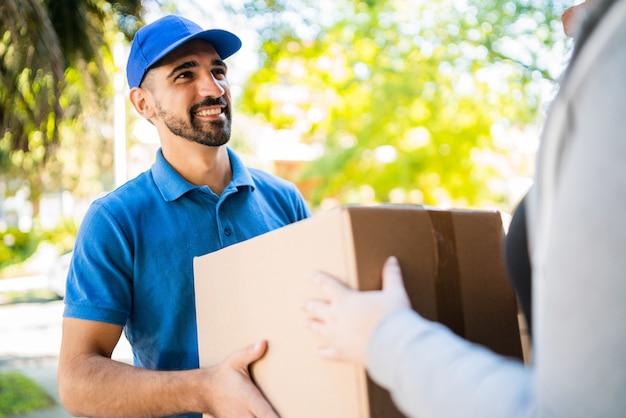 Uomo di consegna che trasportano pacchi durante la consegna a domicilio.
