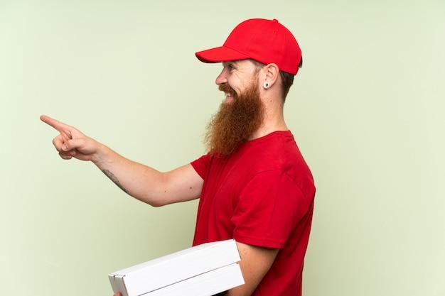 Uomo di consegna con barba lunga su sfondo verde isolato che punta verso il lato per presentare un prodotto