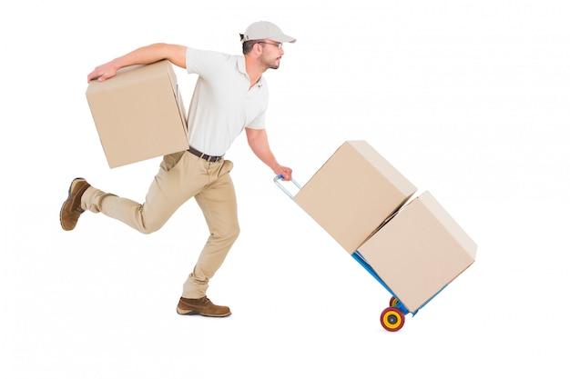 Uomo di consegna con carrello di scatole in esecuzione