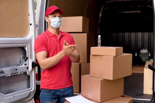 Uomo di consegna con disinfettante per le mani