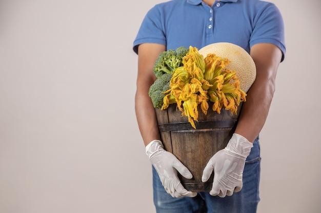 Uomo di consegna con guanti con cesto di frutta e verdura