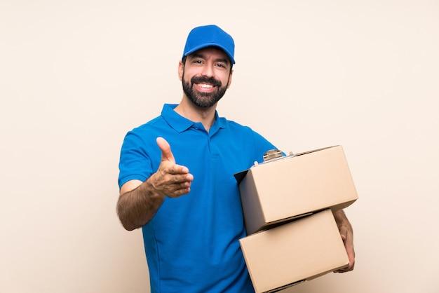 Uomo di consegna con la barba che stringe la mano per chiudere un buon affare