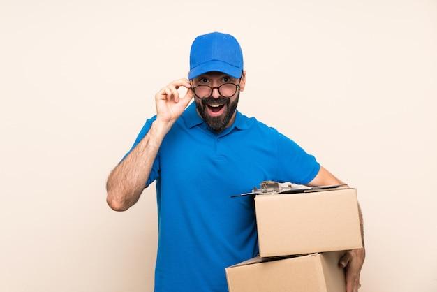 Uomo di consegna con la barba con gli occhiali e sorpreso